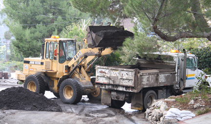 County workers removed mud and debris that flowed down Canyonside Road during last week's cloudburst. The downpour, though quick, was strong enough to carry rocks and dirt onto local roads.