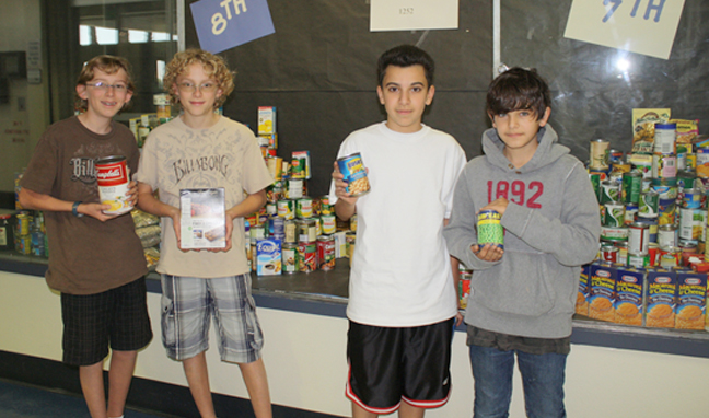 Rosemont Middle School students collected close to 1,300 cans of food to donate to the Crescenta Valley Sheriff's Station Annual Food and Toy Drive. They delievered the food on Tuesday to the sheriff volunteers. From left, Joseph and Michael Tinglof, Edrick Tanahan and Arne Mael. Photo by Mary O'KEEFE
