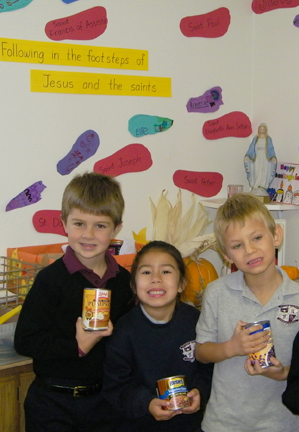 Kindergarteners help in the food drive From left Jeffrey Lewis, Arianna Blandon and Andrew Schneider bring in their cans. Photo courtesy of Tricia Flynn