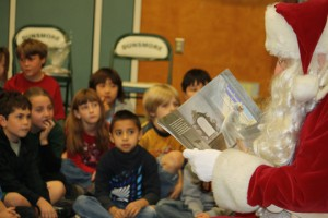 "Photos by Mary O'KEEFE Students at Dunsmore Elementary School were treated to a visit by Santa Claus on Friday. Santa read ""Twas the Night Before Christmas"" written by Clement Clarke Moore. After the reading the students and teachers joined Santa in a round of Christmas carols."