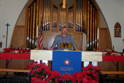 Pastor Gary Heltsley of Mt. Olive Lutheran Church stands in front of the church's signature pipe organ.  Photo by Shana LiVIGNI