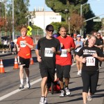 Runners turn the corner toward the finish line at the Thanksgiving Day Run and Food Drive in La Cañada on Thanksgiving day.