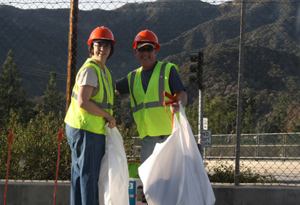 Armed with trash bags, safety vests and hard hats, Sandy Switzer and Steve Pierce helped with the clean up of the La Crescenta Avenue 210 freeway offramp. Members of various civic groups, including the CV Town Council and chamber of commerce, meet monthly to help keep the ramp free of debris. On Saturday, Pierce and Switzer were joined by Neil Ryan and Todd Thornbury.  Photo by Robin GOLDSWORTHY