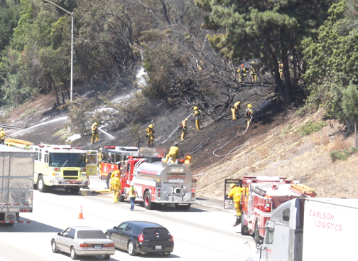 Photo by Danny GOLDSWORTHY Fire crews work the hillside of the eastbound Foothill (210) Freeway east of Pennsylvania Avenue on Tuesday afternoon.