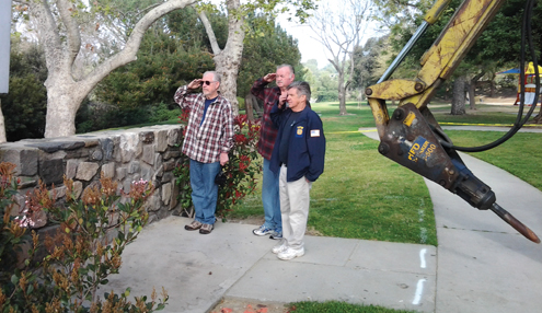 Photos by Mary O'KEEFE Veterans, from left, Mike Baldwin, Warren Spayth and Roy Allmon, salute the old Two Strike Park Memorial Wall as the bulldozer waits. Funds have been raised for a new memorial wall.