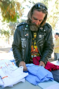 Photos by Michael J. ARVIZU Michael Stephen Cento of Sunland looks for clothing in his size during Montrose Church's homeless outreach in Sunland Park on Saturday, March 30.
