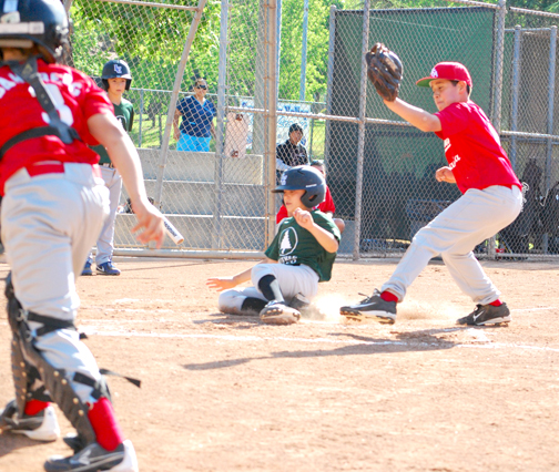 David Case slides in to home plate just ahead of the tag by Francisco Robles.