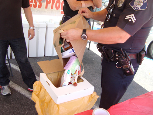 A Glendale police officer dumps a bag of medication that was surrendered as part of Drug Take Back Day on Saturday into a receptacle. The collected drugs will be burned at another location.