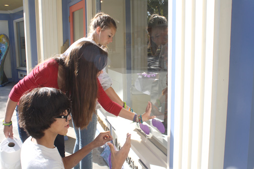Photo by Mary OKEEFE Members of Prom Plus Club paint a window purple on Saturday reminding the public of the upcoming Relay For Life taking place May 11-12.