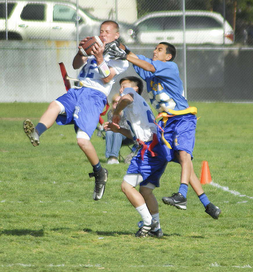 Photos by Ed HAMILTON Rosemont's Tyler Hill catches a down field kick, with Joeseph Suh and Wilson's Idean Samirami. Flag Football game CV Rosemont Middle School versus Glendale Wilson Middle School.