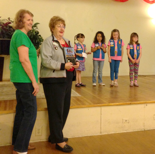 Courtesy of Gloria LEE Photo Caption: Marianne Jennings, Daisy troop leader, looks on as LCWC president Carol Huntwork displays a plaque of appreciation presented to her by Girl Scout Daisies.
