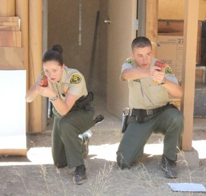 Explorers Shannon Snyder and Kevin Lentz are shown with simulated guns drawn during a competition.