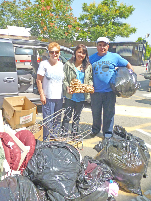 La Crescenta Woman's Club member Gloria Lee delivers a vanload of clothing to MEND, a charity  in San Fernando. The donation was accepted by Veronica Soto, clothing department manager, and volunteer Roberto Cerecer.