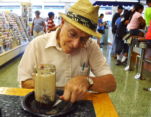 Photos by Brandon HENSLEY Mayer Alson employs his chip-away method to a classic Jerry's ice cream soda at Desoto Pharmacy owned by La Crescenta resident Dave Meyers.
