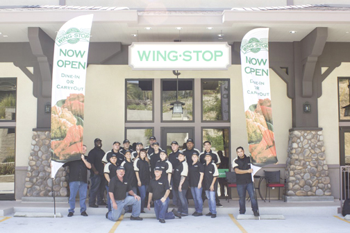 Photo by  IanArtistry.com Former Glendale community police officer Jerry Uebel, front left, and Jay Hoehn, front right, pose with their Wingstop staff in front of the new restaurant that has opened in the area.