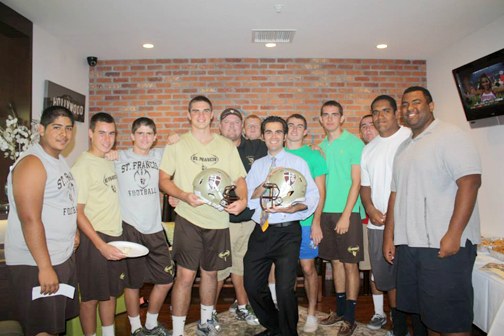 "Dr. Rozheh Babaan with the St. Francis High School football team during ""St. Francis Night at the Studio."""