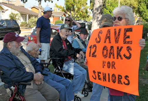 Photo by Dan HOLM Four veterans (seated above at a recent protest) who thought they would spend the rest of their lives together at Twelve Oaks are looking at relocating now that the property is for sale.