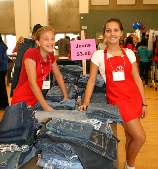 Ticktockers Maddie Bohman and Isabella Apodaca organize a table piled with blue jeans during the giant sale.