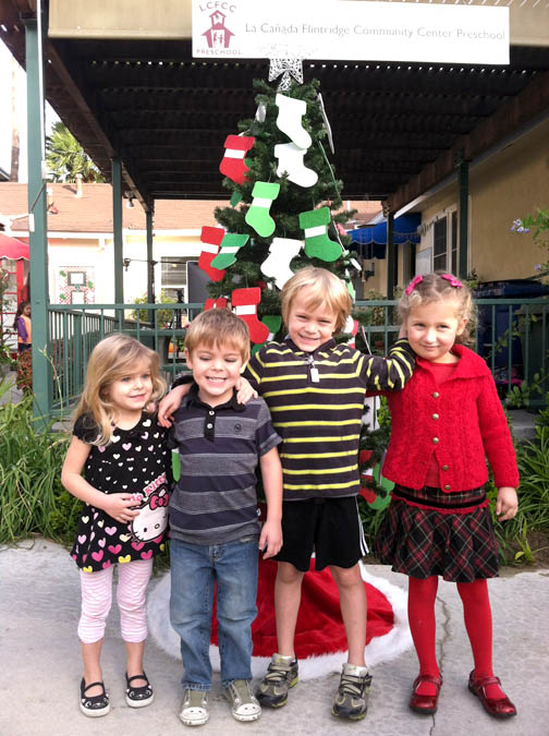 RIGHT: La Cañada Flintridge Community Center Preschool students Teagan and Parker Jahnke, Scott Perkins and Esme Woerner are among those who are experiencing the joy of giving in support of this year's Adopt-A-Family program benefiting families from Children's Hospital Los Angeles.