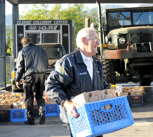 File photo CV Sheriff's Station volunteer Don Williams hauls a crate of food to a waiting sheriff's vehicle during last year's toy and food distribution.