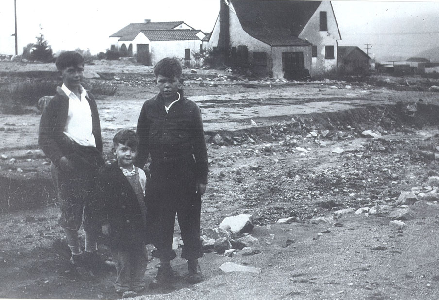 Photo courtesy of the Historical Society of the Crescenta Valley The 3000 block of Prospect Avenue was covered in mud and debris on New Years Day 1934, the day after the lethal New Year's Eve flood. Bob Crowe, the youngest of the three brothers shown here, had just spent the night up in the attic of their house seen to their right in the background.