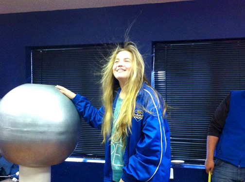Seventh grader Brennah Bronk gets a charge from the static electric ball during an indoor science lab.