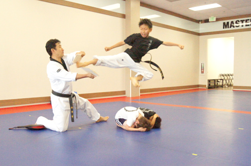 A student breaks a board with a flying kick.