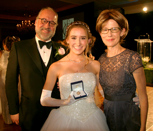 Photo by Janet Lazier, NCL Glendale Daisy Marilyn Beckner, center, with her parents Michael Beckner and Linda O'Callaghan, displays the Golden Oak Leaf award presented to the Ticktocker who, during her six years served the most volunteer hours at Twelve Oaks Lodge.