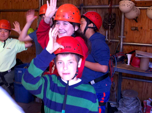 Sixth graders Sean Metz (front) and Sasha Barron (rear) perform a safety check before taking their zip line ride.