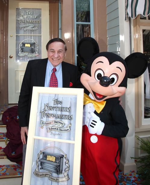 Photo Courtesy Steve Moyer, PR Richard Sherman, left, stands with Disney representative Mickey Mouse, right, at the presentation ceremony for his honorary window on Main Street, U.S.A.