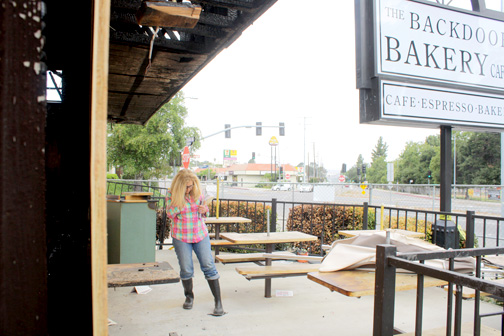 Deborah Goodale takes a call as she surveys the damage to the Backdoor Bakery and Cafe.