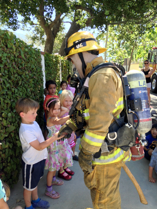 LCFCC preschool student Mason Marchetti gets a lesson in firefighting from local firemen.