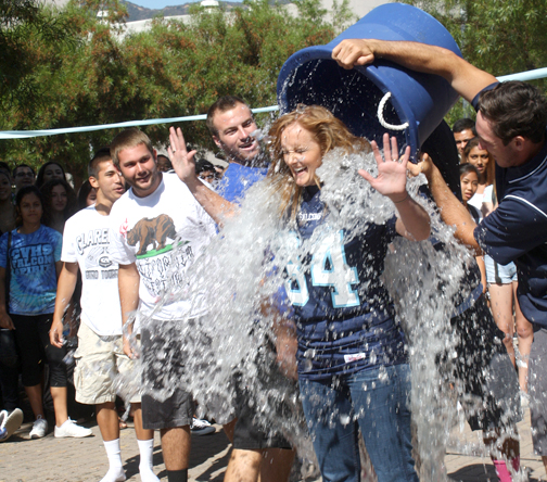 Photo by Mary O'KEEFE CVHS principal Linda Junge meets her Ice Bucket Challenge with help from members of the varsity football team.