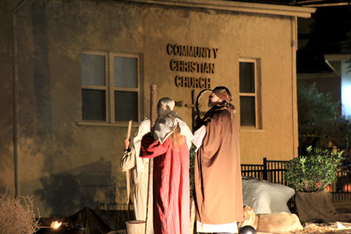 The three wise men approach the manger.