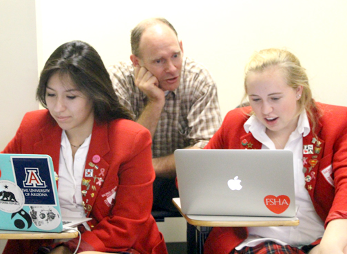 "Ty Buxman, Science Dept. chair, helps his physics students during the ""Hour of Code."""