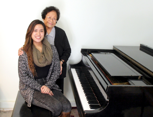 Music teacher Celia Celis, standing, helped deaf student Mara Ladines master the piano.