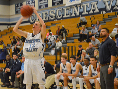 Kyle Currie goes for the shot while Coach Shawn Zargarian looks on. Currie scored 21 points.