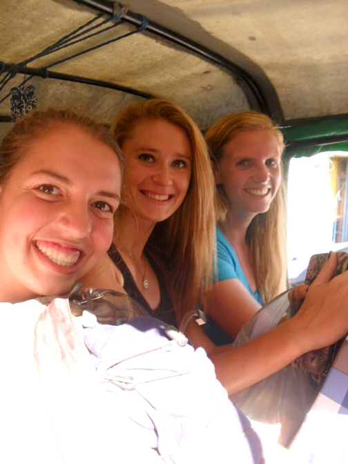 With girlfriends, Chamber rides in the back of a motortaxi.
