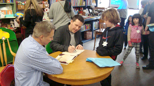 """Kid Sheriff and the Terrible Toads"" author Bob Shea signs a copy of the book for a fan while illustrator Lane Smith waits his turn."
