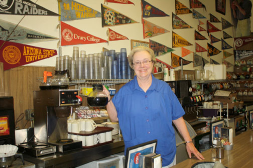 Wanda Bergstrom stands in front of the dozens of pennants hung in the City Hall Café.
