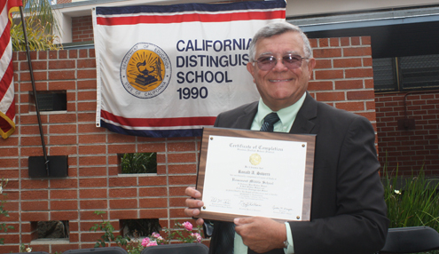 Photo by Mary O'KEEFE Ron Sowers holds up his diploma presented to him by Principal Dr. Cynthia Livingston. Wednesday was the last promotion ceremony that Sowers will oversee since he retired from the school as assistant principal.