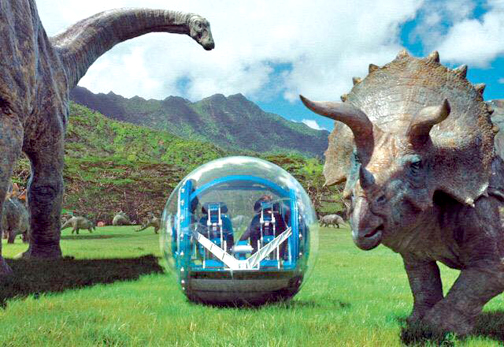 Photo Courtesy Universal Pictures Tourists in a glass bubble run the plains of Jurassic World with Diplodocus, left, and Triceratops.