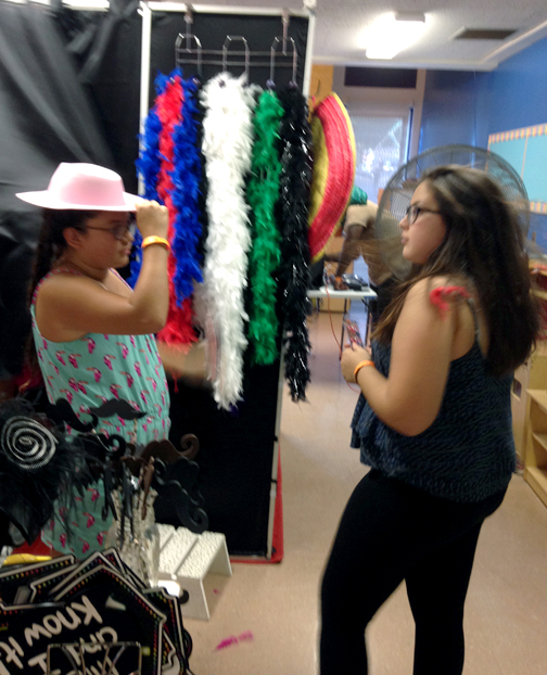 Alyssa Paniagua, 13 and Maya Berkovitz, 13, try on hats before popping into the photo booth at Orange Fest held Saturday at CV Park.