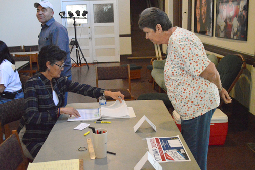 Photo by Brandon HENSLEY Ines Chessum, seated, checks in a voter during the Crescenta Valley Town Council elections held on Friday and Saturday at St. Luke's of the Mountains.