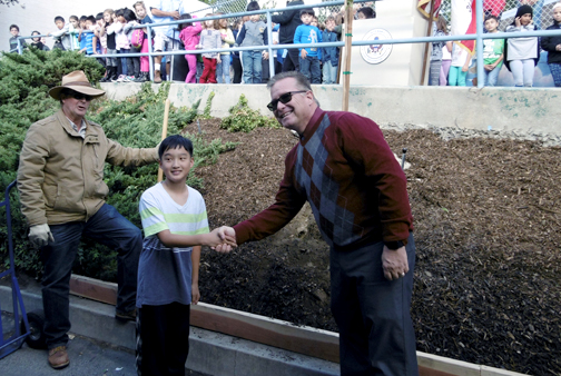Steven Carris, a Valley View student, shakes hands with school principal Dr. Brook Reynolds, after placing third in the 2015 I Love My Neighborhood poster contest.
