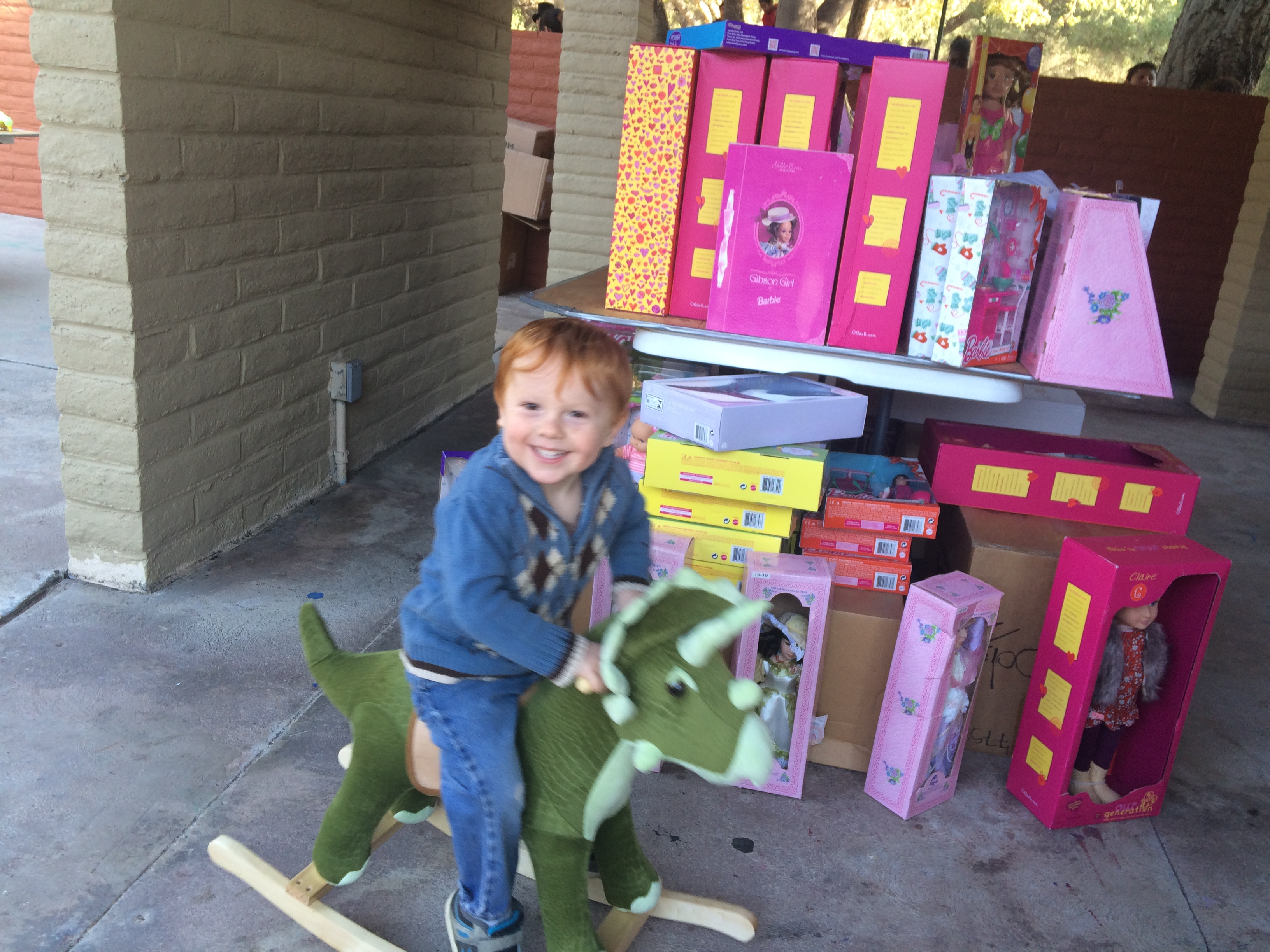Photos by Mary O'KEEFE Zeke Cross, 3, straddles his new most favorite toy – a rocking stegosaurus – that he chose at CV Park on Saturday morning as part of the CV Sheriff's Toy and Food Drive.