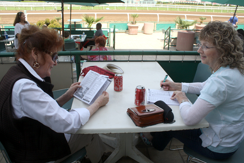 Bobbi Parker and Lynda Bayly go over the racing program.