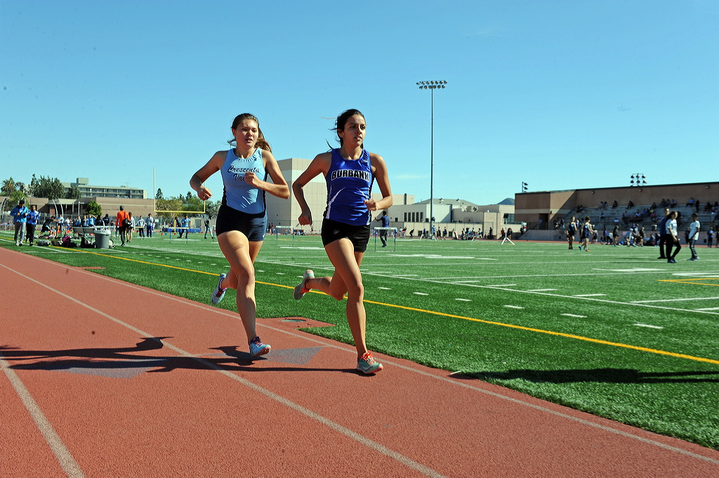 Grace McAuley and Candela Fernandez work the 1600 race.