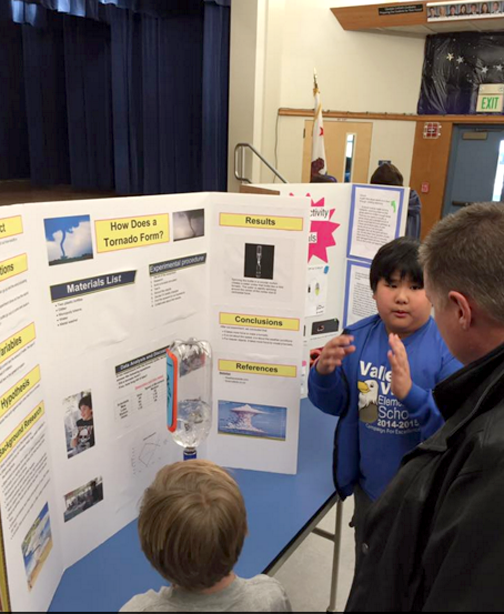 Student, Bryson, explaining his findings to principal, Dr. Reynolds
