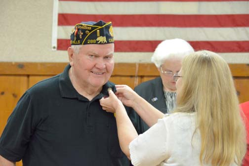 Photos by Dick CLUBB Lynn McGinnis receives his commemoration pin from a member of the DAR during a May American Legion Post 288 meeting.